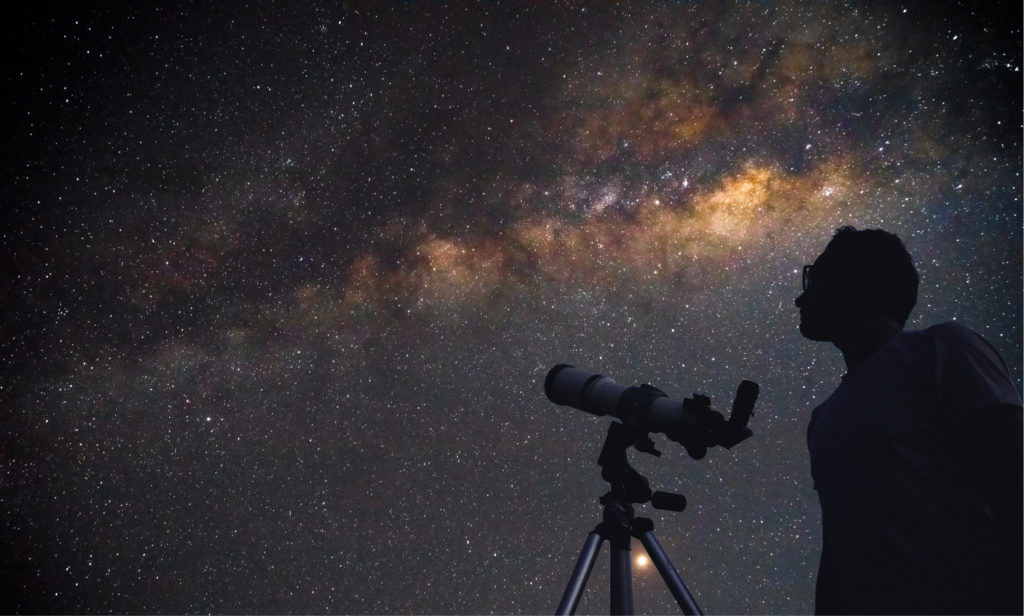 Astronomer with a telescope watching the galaxy.