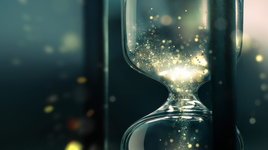 Close up of hourglass with shining sand.