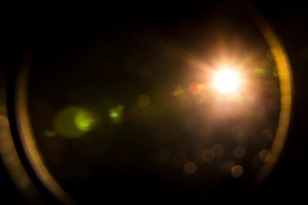 Abstract lens flare yellow light over black.