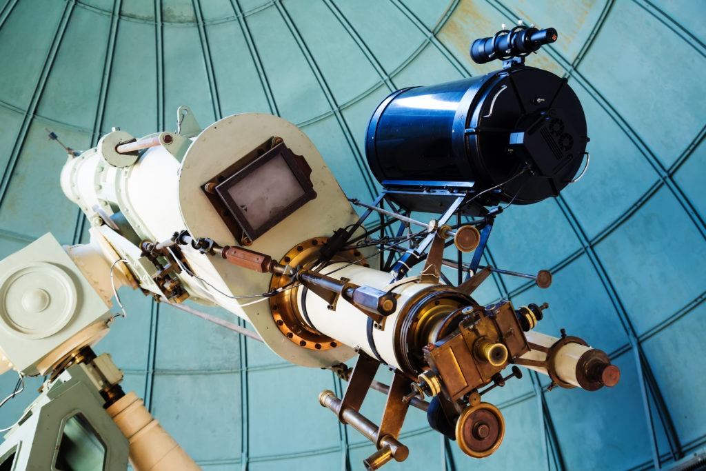Close-up view on oculars of large professional telescope located indoors.